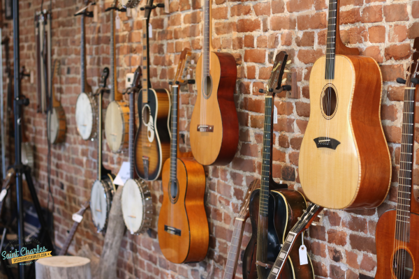 Guitars hanging on a brick wall at Driftwood Music in St. Charles, MO