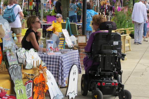 person in wheelchair browsing stall at St Tammany Community market