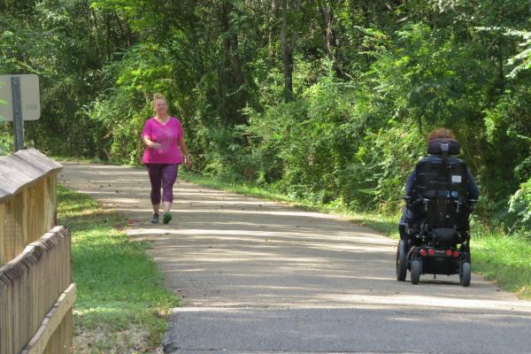 A person using a wheelchair on the Tammany Trace trail
