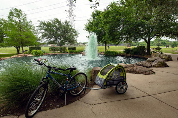 Bike and rickshaw in front of the water feature at Oyster Creek Park.