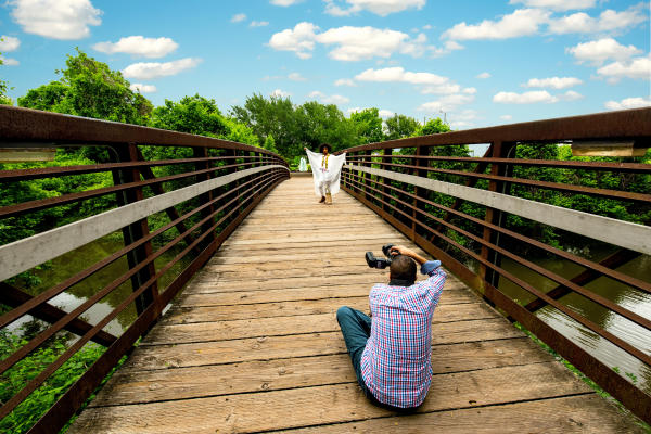 Photographer taking photo of model on the bridge leading to the water feature at Oyster Creek Park.