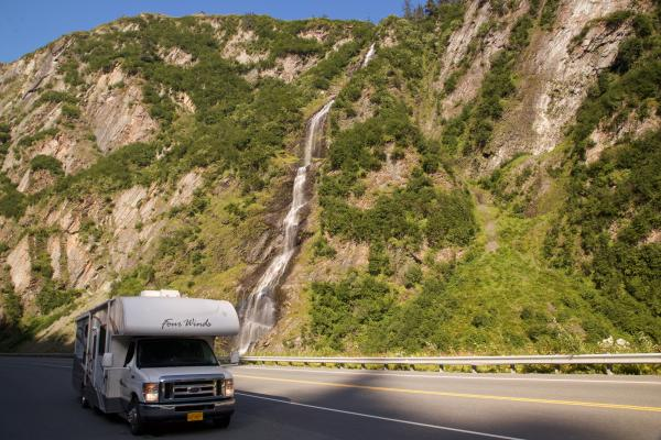 an rv parked alongside a highway by a waterfall in a canyon