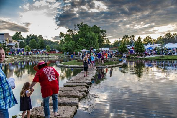 People walking across stepping stones at the Lenexa BBQ Battle