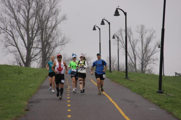 A group of runners pace through the morning fog along the Mississippi River Levee Path.