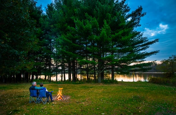 Couple sitting by the water at campground