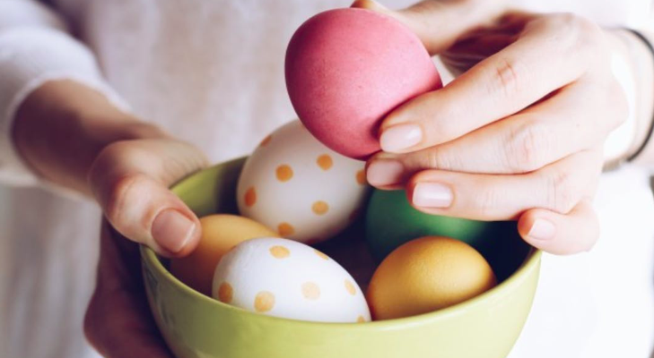 Hands holding a green bowl full of polka dot and colored Easter Eggs