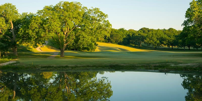 Lush trees surrounding a pond at the Meadowbrook Golf Course creates a tranquil scene