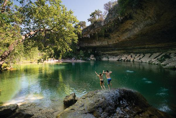Couple jumping into the water at Hamilton Pool
