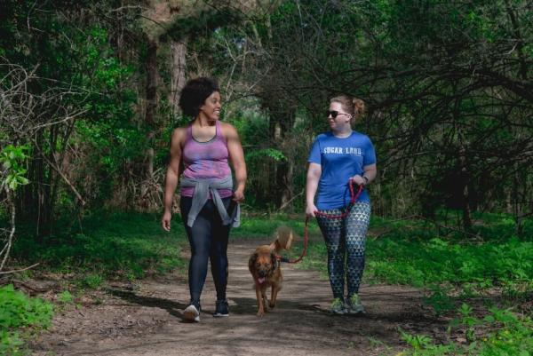 Two girls walking a dog at one of Cullinan Park's trails.