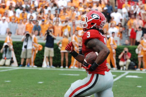 UGA football player running with the ball at a Georgia football game