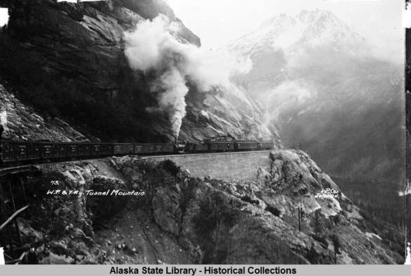 Railroad locomotive and train on side of Tunnel Mountain
