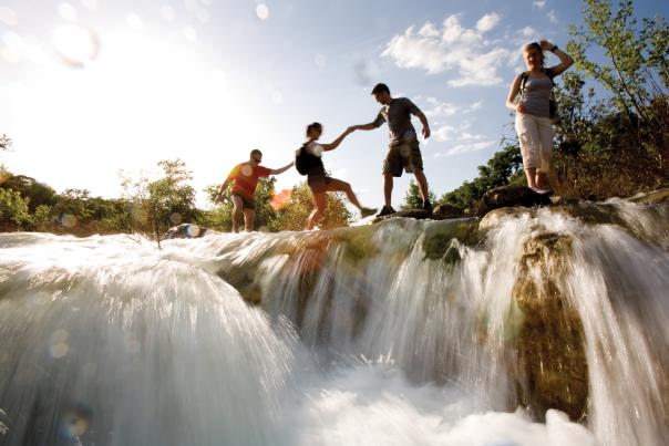four people cross a waterfall while hiking