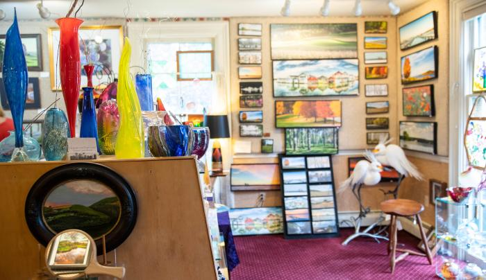 Photo of the inside of Artizanns Gift shop in Naples where the walls are lined with paintings
