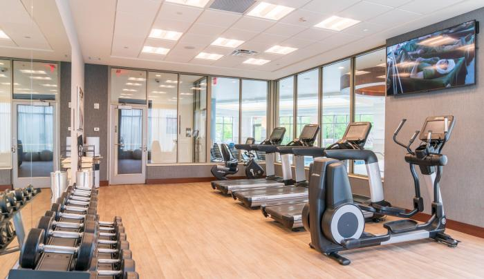24-Hour StayFit Gym featuring cardio equipment with LCD touchscreens