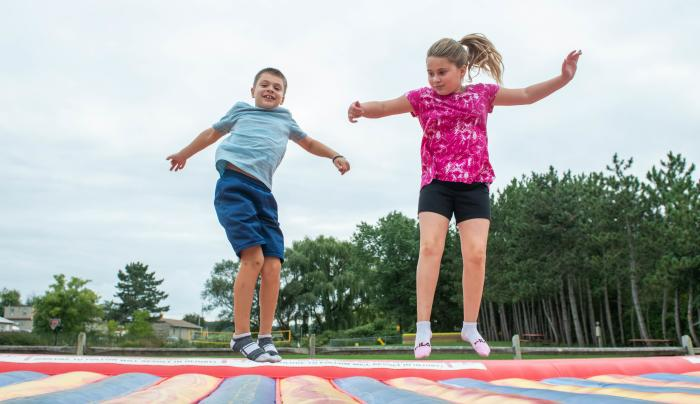 Two kids enjoy jumping on a trampoline at KOA Campground in Canandaigua / Farmington