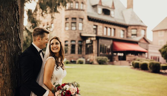 Photo of Bride and Groom by a tree at Belhurst Casle