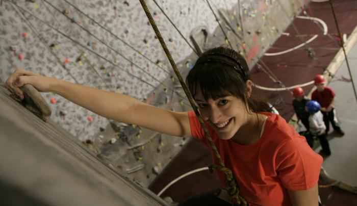 Young woman climbing at RockVentures in Rochester, NY