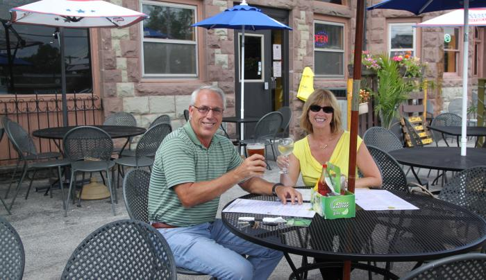 bee-hive-brew-pub-canandaigua-couple-outside-toasting-glasses
