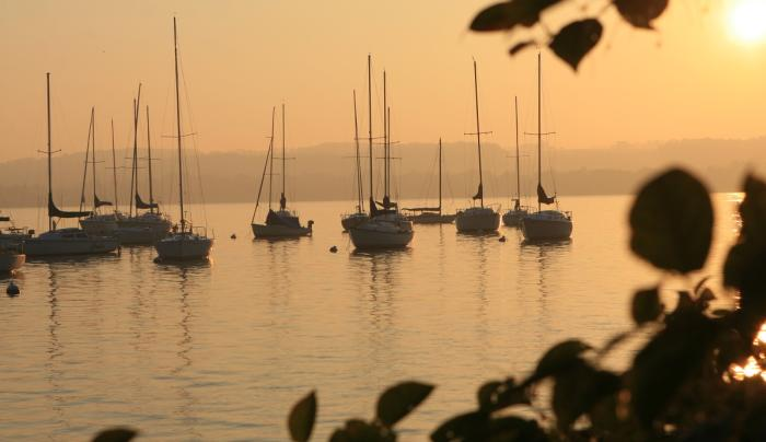 Photo of a sunset overlooking sailboats anchored at a dock on Canandaigua Lake