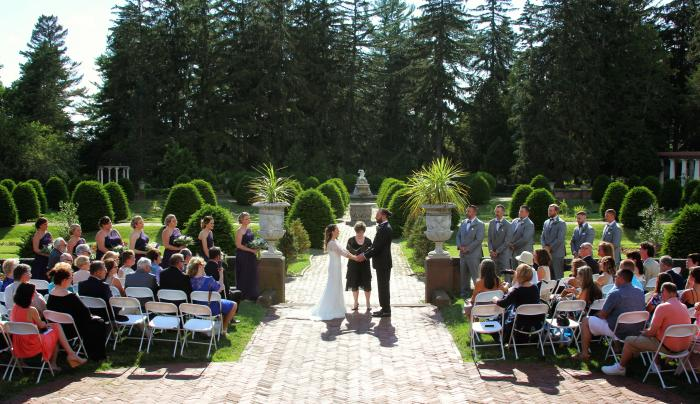 A bride and groom exchange vows during their wedding at Sonnenberg Mansion and Gardens