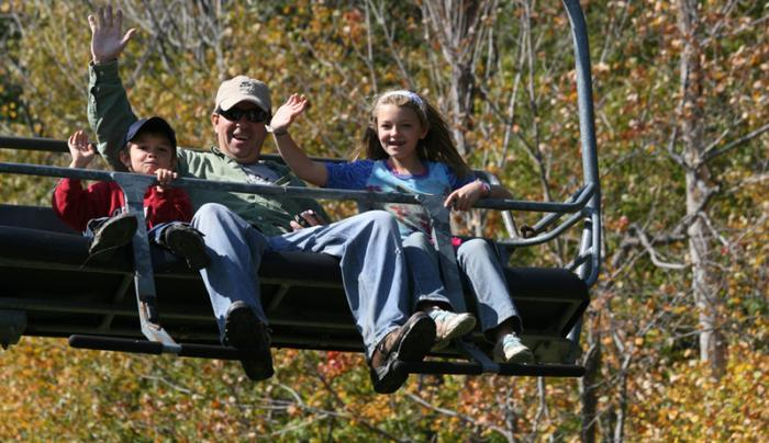 A Family at Bristol Mountain Waves for a photo on the chairlift
