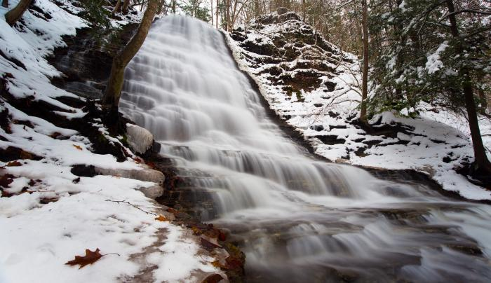 A waterfall rushes during the winter at Grimes Glen in Naples
