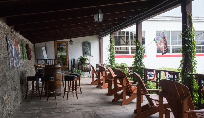 Exterior porch seating area at Hazlitt's Red Cat Cellars in Naples