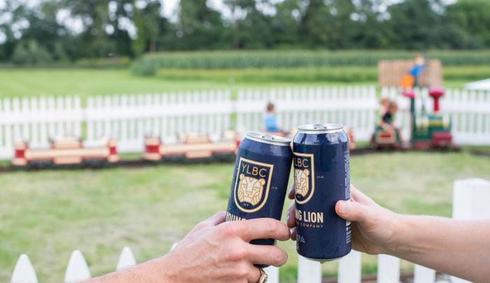 Two people cheer with young lion beer cans at the Pick n' Patch in Stanley