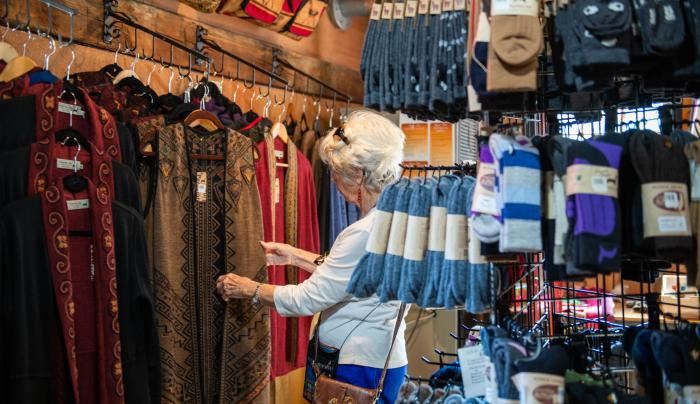 A lady shops for clothing inisde of the Lazy Acres Alpaca shop