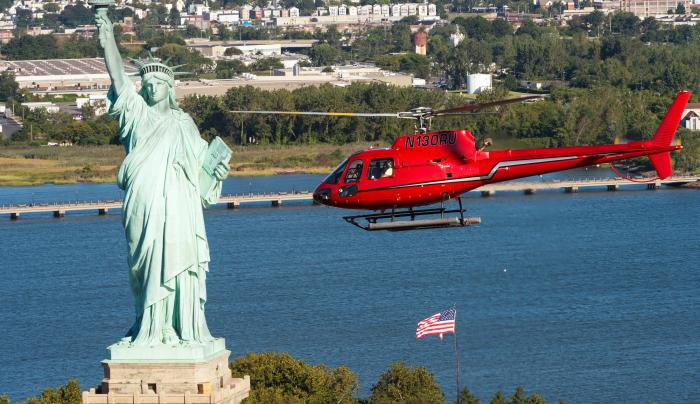 Liberty Helicopter flying by the statue of liberty during the day