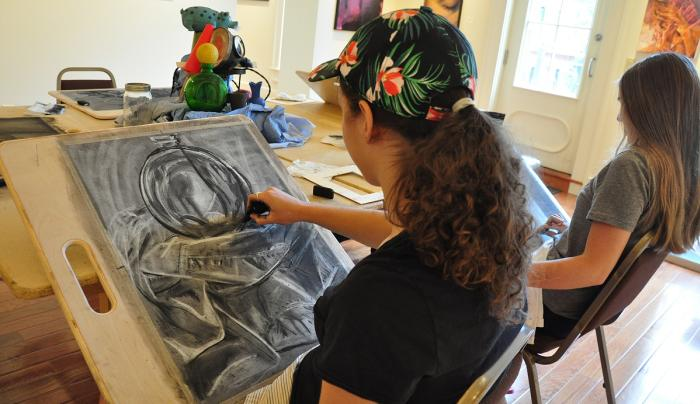 A artist paints a picture at Main Streets Arts in Clifton Springs