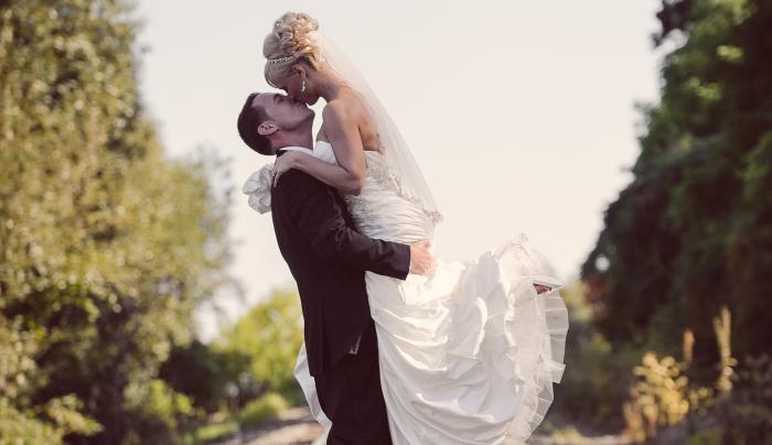 Bride and Groom embracing on railroad tracks that cross near Belhurst Castle