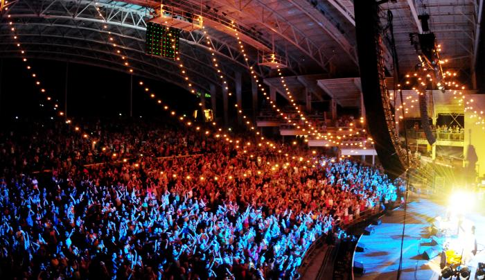 Photo of a crowd lit up red white and blue during a concert at the CMAC Center in Canandaigua