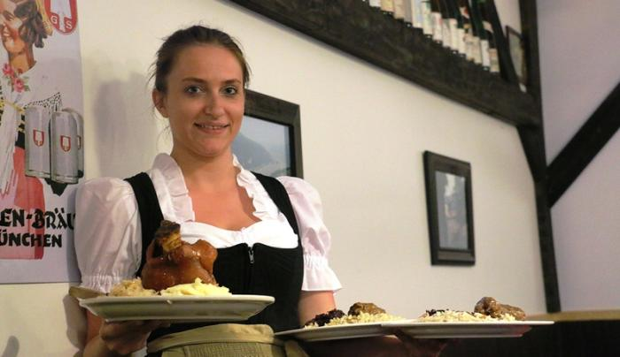 A server poses with two plates in hand at Rheinblick German Restaurant