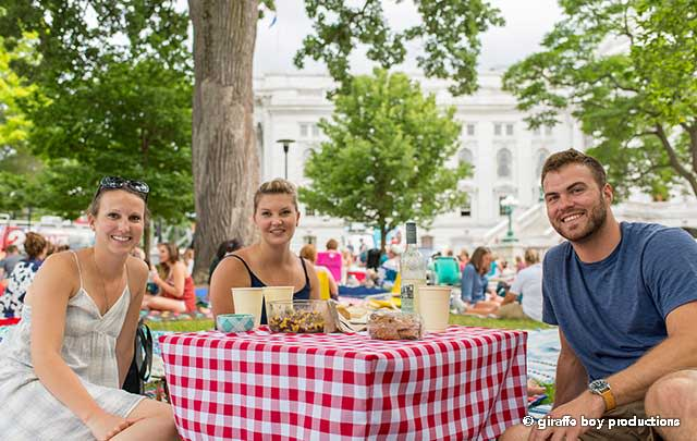 Three people have a picnic around the State Capitol