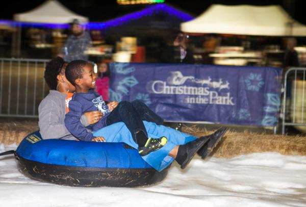 A mother and son sled down a snow hill at Christmas In The Park in College Station