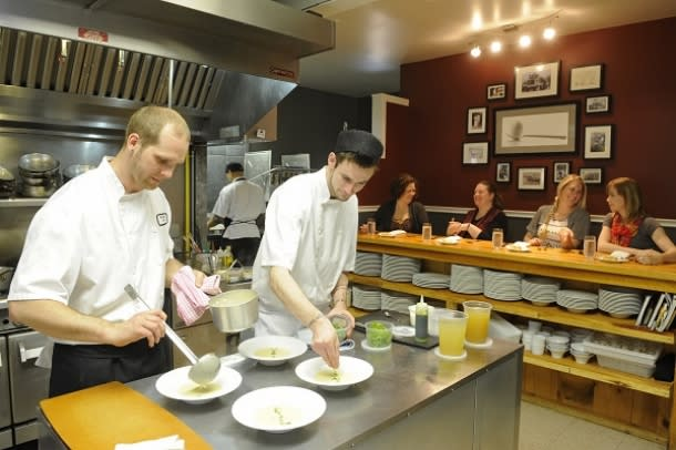 Chefs cooking with customers looking