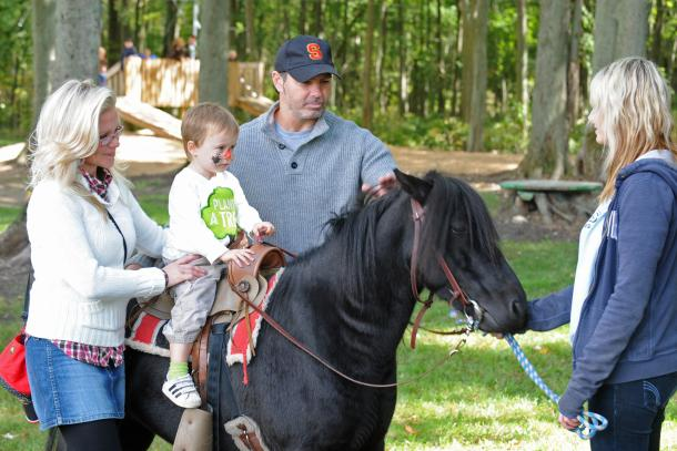 Kid riding horse at Kustermans with family