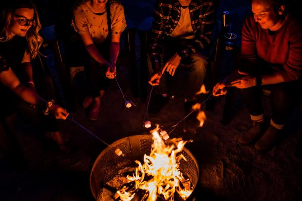 people at roasting marshmellows on campfire