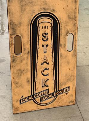 "Rustic sign outside The Stack restaurant that reads ""Local Coffee"" and ""Local Donuts"""