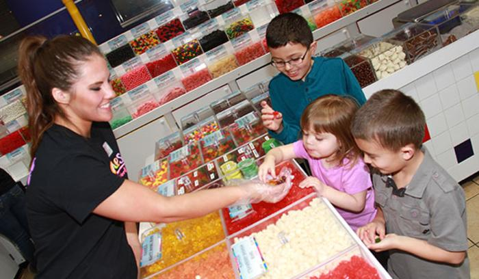 Albanese Candy Factory worker handing candy samples to happy kids