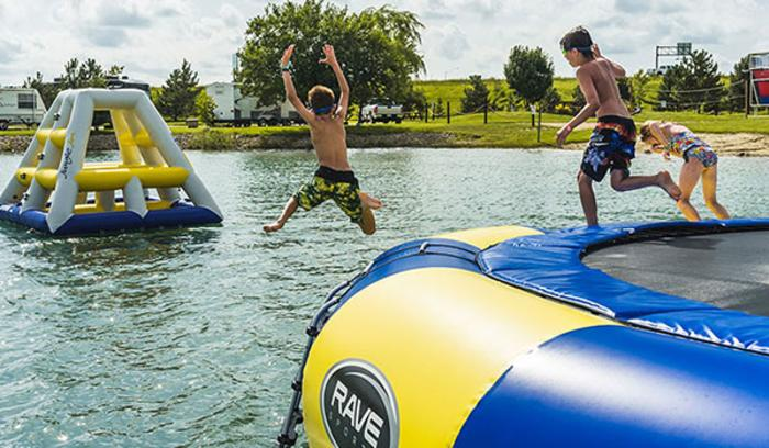 Kids jumping off inflatables into the water at Caboose Lake Campground