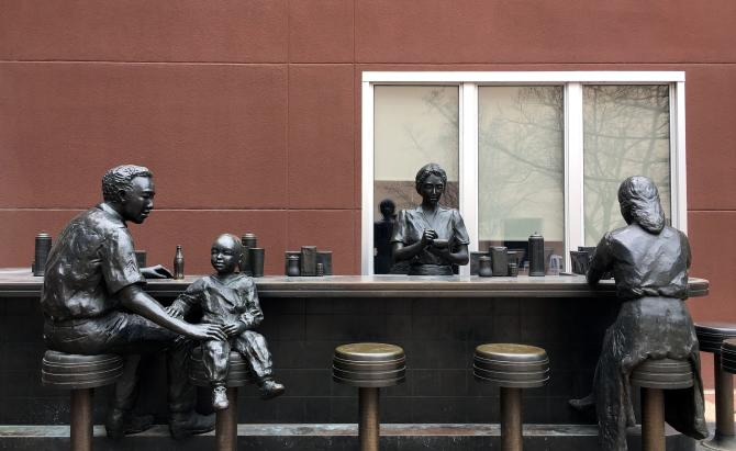 Bronze statue that re-creates a soda fountain that might have been in the store, with a man and a boy sitting at two stools and a woman behind the counter