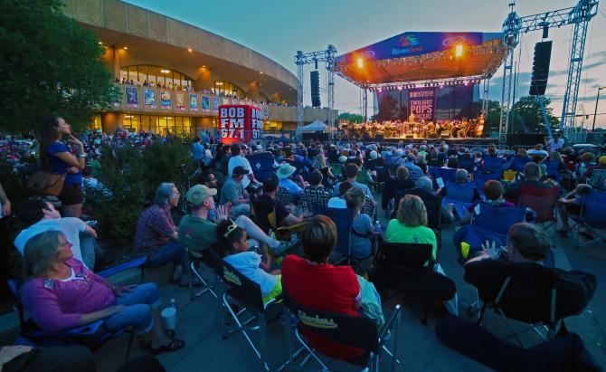 A large crowd of Wichitans sit in lawn chairs around a stage at Wichita Riverfest as part of the Twilight Pops Concert series