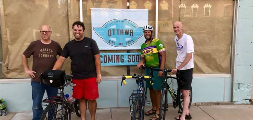Riders pose in front of the Ottawa, KS Bike Shop, opening soon