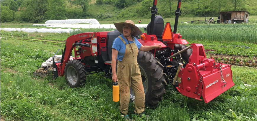 A farmer stands by a tractor during an Asheville Farm to Table Tour