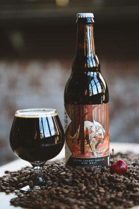 Bottle and glass of dark beer from Wolf's Ridge Brewing sitting atop pile of coffee beans