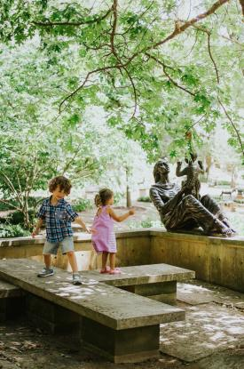 Kids playing with the Mother and Child Sculpture at UMLAUF Sculpture Garden Museum in austin texas