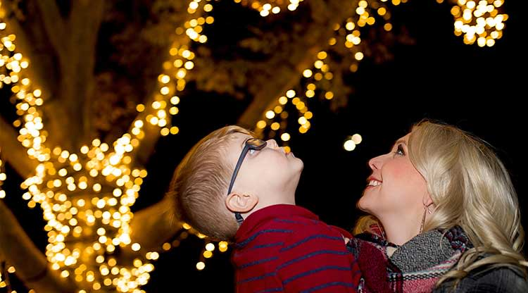 A mom & child enjoy the Luminary Walk at Overland Park Arboretum