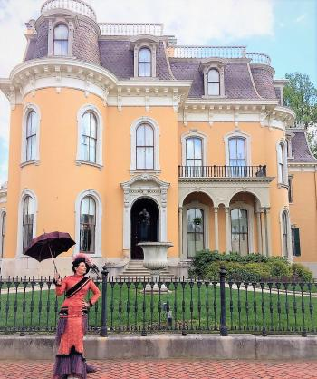 A woman in period Victorian costume outside the Culbertson Mansion State Historic Site.